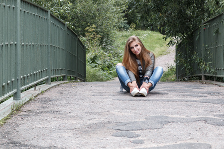 rock n: young beautiful teenager girl is sitting on the track on a bridge, rock n roll. rock style