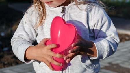 plastic heart: little girl playing with a red plastic heart. she holds it in her hands.