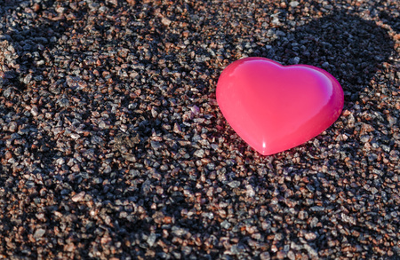 plastic heart: Red plastic heart lies on the sand. pea gravel.