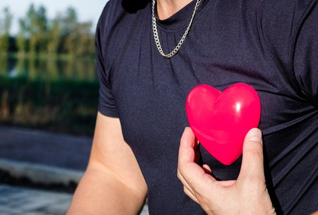 plastic heart: man holding a red plastic heart