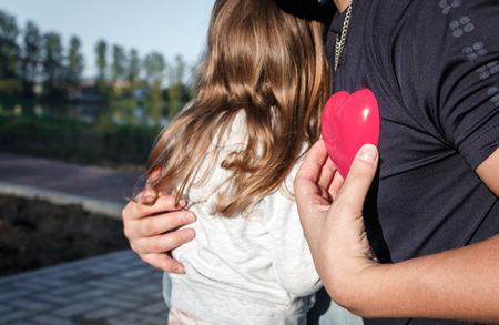 plastic heart: man holding a red plastic heart and hugs child. father and daughter.