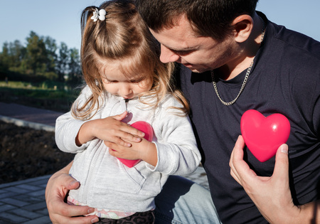 plastic heart: man and baby holding a two red plastic heart. father hugs the daughter.
