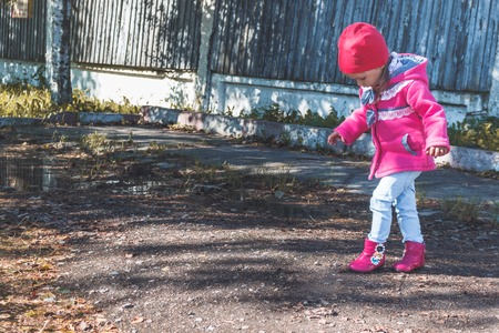 Little girl in a pink coat, jeans and pink boots walking in the park.