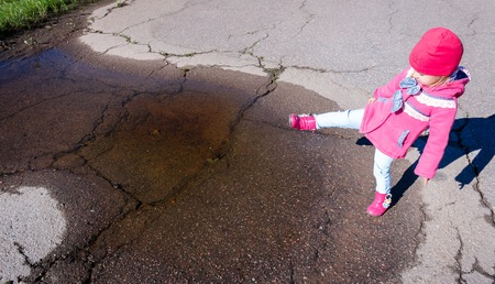 giggling: Little girl in a pink coat, jeans and pink boots walking in the park.