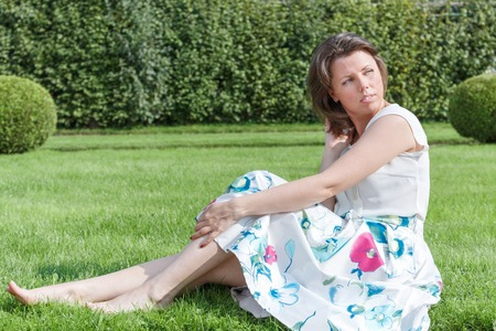 fashion of nice pretty young hipster woman is sitting on green grass in a blouse and long skirt.