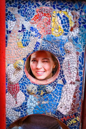 cohesion: womans face in a round hole in the mosaic wall