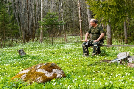 ax man: Springtime is the moment for flower. Snowdrop anemone. man with an ax sitting on a bench in the form of hunting.