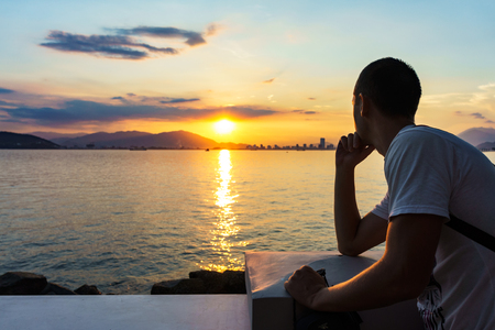 Young man is looking at the sunrise. Stock Photo