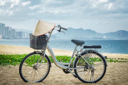 Fahrradabstellplatz im Strandsand. am Fahrradlenker Vietnamesischer Hut hängt. Vietnam.