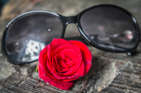 Womens sunglasses and red rose lying on a wooden table. close-up. Stock Photo