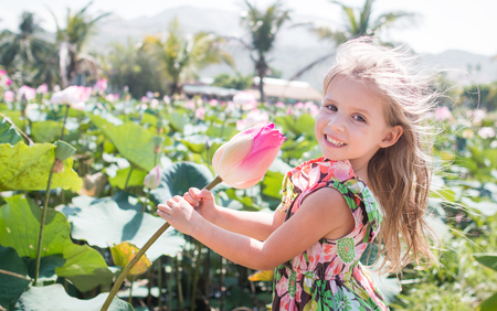 This beautiful waterlily or lotus flower. The girl hold in her hands a flower and smile. Stockfoto