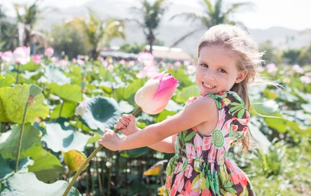 This beautiful waterlily or lotus flower. The girl hold in her hands a flower and smile. Stockfoto - 104525071