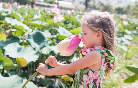 This beautiful waterlily or lotus flower. The girl hold in her hands a flower, sniff it and smile.