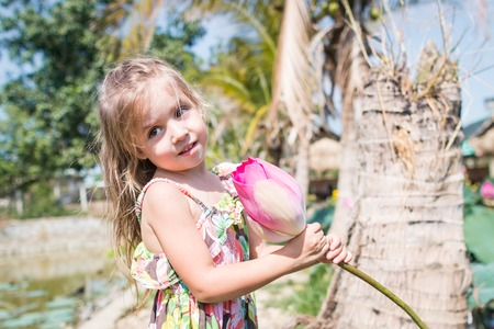 This beautiful waterlily or lotus flower. The girl hold in her hands a flower and smile. Stockfoto - 104524991