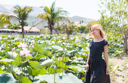 The young girl stay in the lotus pond and smile. Standard-Bild
