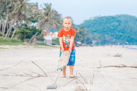 cute smiling little boy walking with paddle at the beach enjoying active vacation at the tropical island, south pacific. Foto de archivo