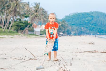 ragazzino sorridente sveglio che cammina con la pagaia alla spiaggia che gode della vacanza attiva all'isola tropicale, pacifico del sud. Archivio Fotografico