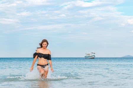 beautiful girl standing waist-high in the sea.