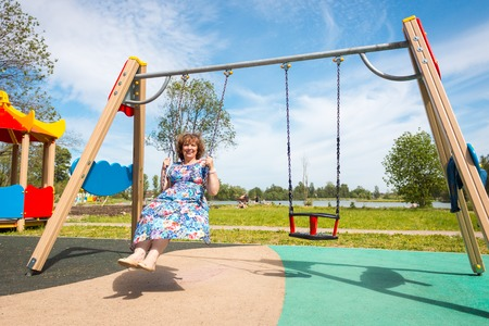 grandmother. old woman riding a swing in the playground