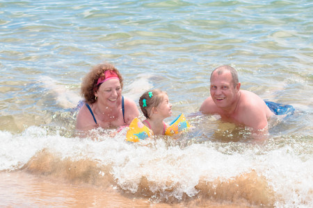Grandparents And Granddaughter swimming in the sea, they smile and happyness.
