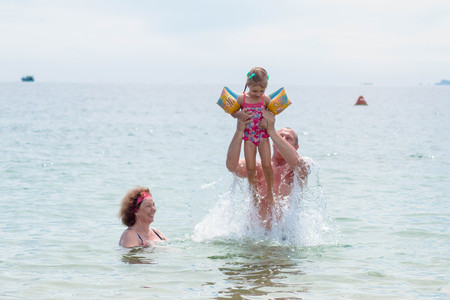 Grandparents And Granddaughter swimming in the sea, they smile and happyness