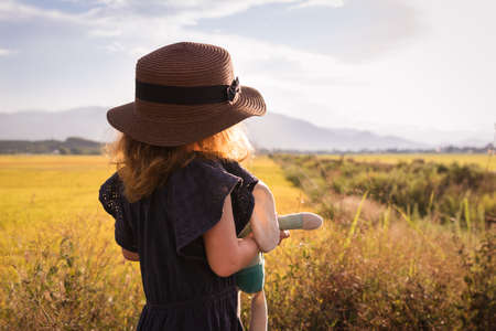 Child girl in straw hat. Cute kid with soft rabbit toy looking at nature lanscape background. Adventure travel concept in retro style