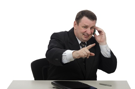 Man sitting at office desk and talking on mobile phone photo