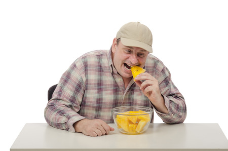 Village man in a baseball cap biting yellow watermelon photo