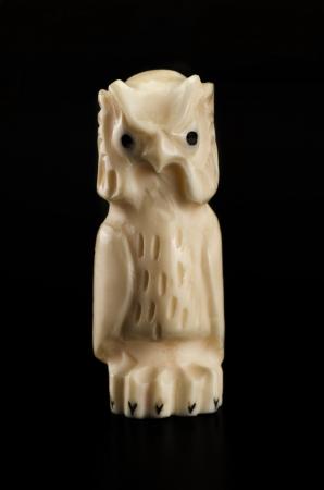 Hand carved bone owl on black Stock Photo