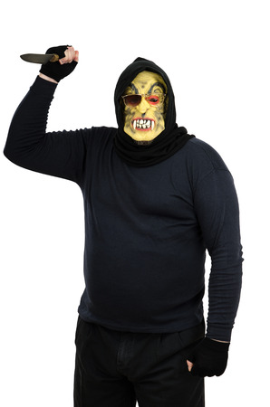 Maniac in a mask waves a knife Stock Photo