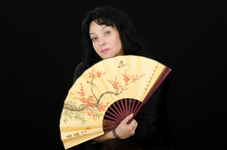 Thoughtful black haired woman with japanese fan photo
