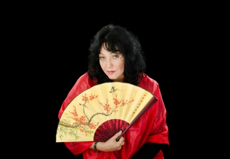 Woman with fan looks askance photo