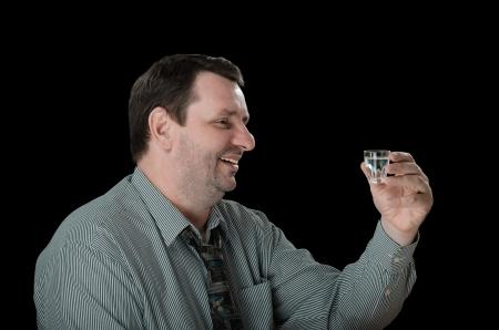 tucker: Smiling man holds shot of vodka Stock Photo