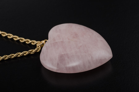 chatoyant: Rose quartz heart with golden chain on black