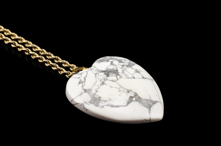 chatoyant: White howlite heart with golden chain on black Stock Photo