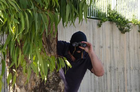 Footpad in balaclava stares at you through binoculars from an ambush