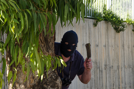 Footpad in black balaclava waiting in ambush with an kitchen hatchet