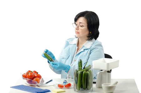 Phytosanitary technician measuring length of cucumber in the laboratory Stock Photo - 26931438