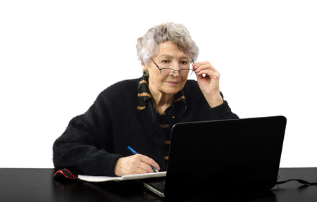 grey haired: Old grey haired teacher carefully listening to the student during online class Stock Photo
