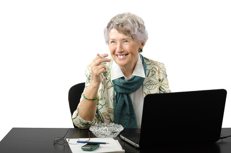 Amazing old business woman working on laptop computer and asks lighter Stock Photo - 27522930