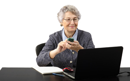 grey haired: Smiling grey haired old business lady calling by cell phone during skype conversation