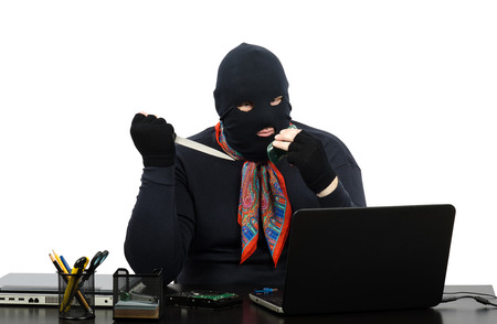 Robber in balaclava with knife talking on the cell phone from robbed office photo