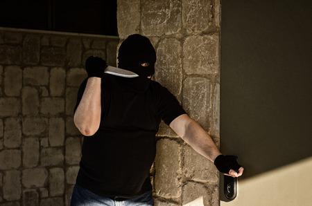 Killer with big knife ambushing behind a home door Stock Photo
