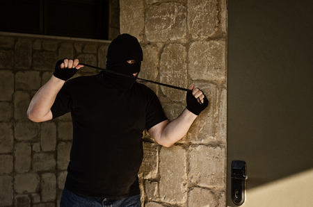 Murderer in balaclava ambushing behind a door with rubber noose Stock Photo