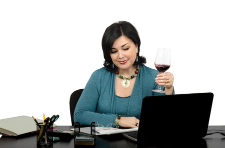 Attractive mature businesswoman surfing favorite websites on her laptop while enjoying a glass of red wine after a long day Stock Photo - 28806428