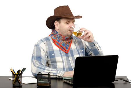 news online: Cowboy looking latest news online on laptop and drinking whiskey Stock Photo