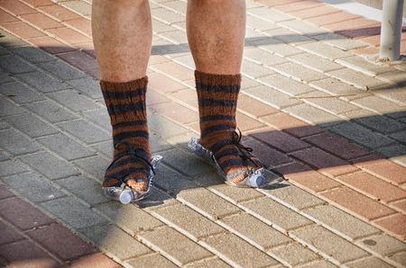 Tramp feet wearing in knitted socks standing in plastic bottle shoes photo