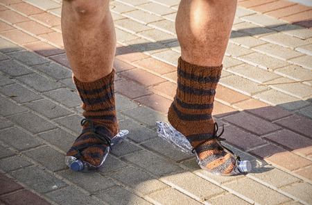outcast: Dancing feet of the homeless in knitted socks on paving stone Stock Photo