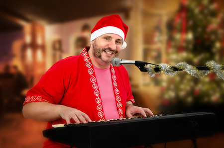 Portrait of bearded mature man in Santa Claus costume playing digital piano and singing Stock Photo - 29875312