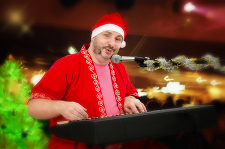 perky: Photo of perky mature man in Santa Claus costume playing electric piano and singing Stock Photo
